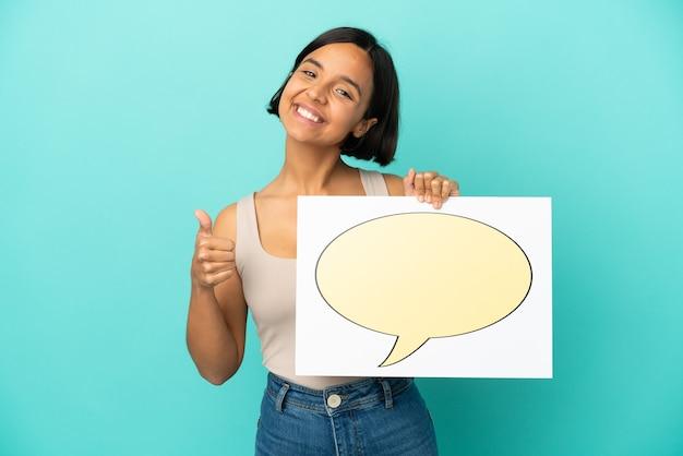 Молодая женщина смешанной расы изолирована на синем фоне, держа плакат с значком речевого пузыря с большим пальцем вверх