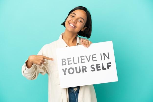 Молодая женщина смешанной расы изолирована на синем фоне, держа плакат с текстом верю в себя и указывая на него