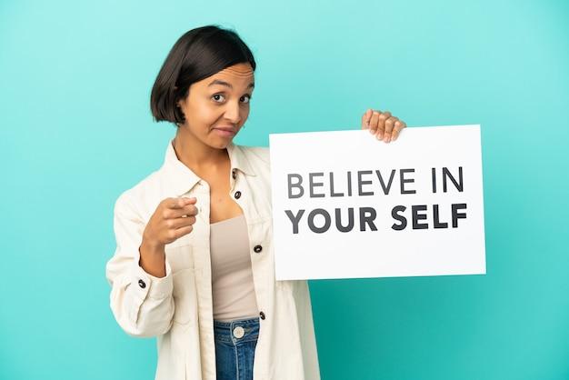 파란색 배경에 격리된 젊은 혼혈 여성은 자신을 믿으라는 문구가 적힌 플래카드를 들고 앞을 가리키는