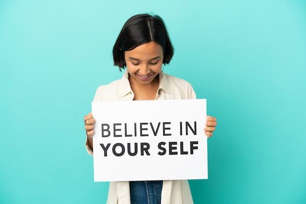 Молодая женщина смешанной расы изолирована на синем фоне, держа плакат с текстом верю в себя