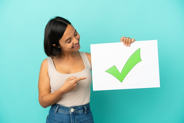 텍스트 녹색 확인 표시 아이콘으로 현수막을 들고 그것을 가리키는 파란색 배경에 고립 된 젊은 혼혈 여자