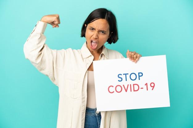 Молодая женщина смешанной расы, изолированная на синем фоне, держит плакат с текстом stop covid 19 и делает сильный жест