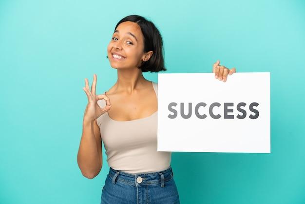 텍스트 성공과 현수막을 들고 승리를 축하하는 파란색 배경에 고립 된 젊은 혼혈 여자