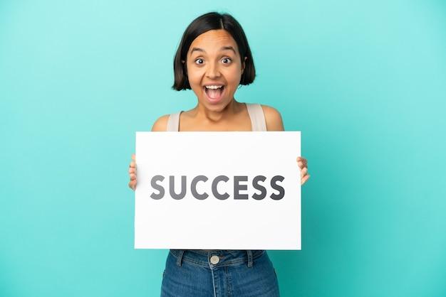 Молодая женщина смешанной расы изолирована на синем фоне, держа плакат с текстом успех с удивленным выражением лица