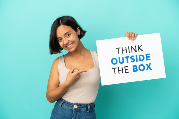 텍스트와 현수막을 들고 상자 밖에 서 그것을 가리키는 파란색 배경에 고립 된 젊은 혼합 된 인종 여자