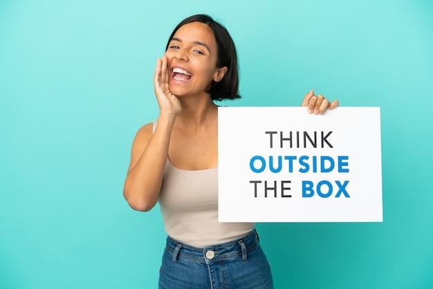 텍스트와 현수막을 들고 상자 밖에서 생각하고 외치는 파란색 배경에 고립 된 젊은 혼합 된 인종 여자