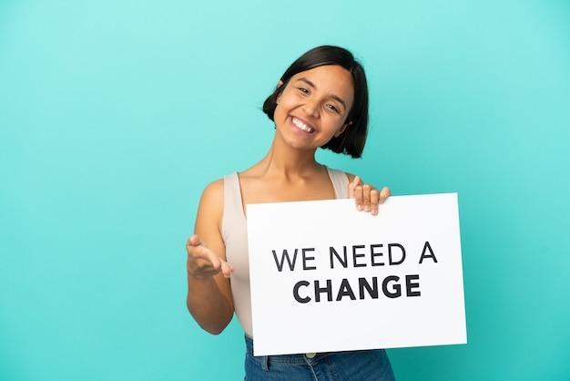 テキストとプラカードを保持している青い背景で隔離の若い混血の女性私たちは取引を行う変更が必要です