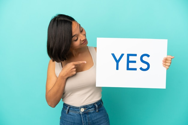 Yesとテキストのプラカードを保持し、それを指している青い背景に分離された若い混血の女性