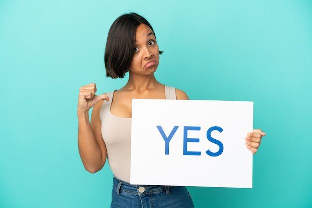 誇らしげなジェスチャーでyesというテキストのプラカードを保持している青い背景で隔離の若い混血の女性