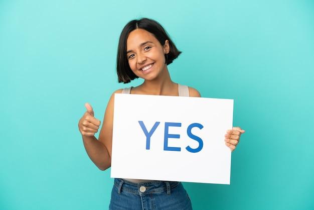 親指を上にしてテキストyesのプラカードを保持している青い背景で隔離の若い混血女性