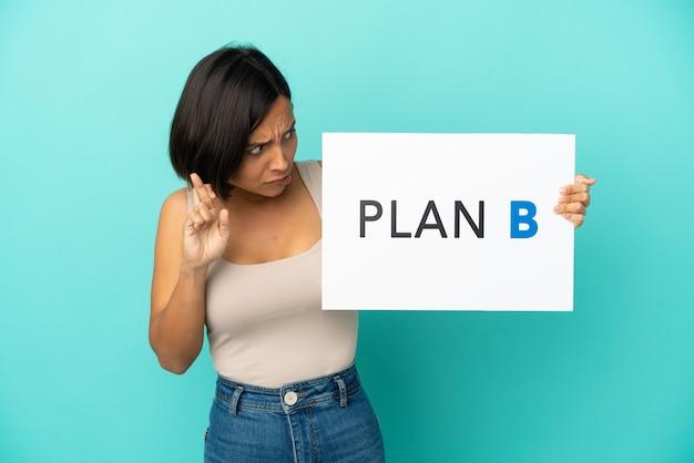 指を交差させてメッセージplanbのプラカードを保持している青い背景で隔離の若い混血の女性