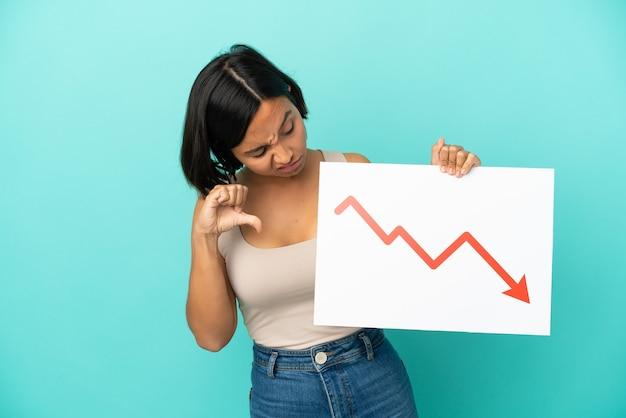 감소 통계 화살표 기호로 기호를 들고 나쁜 신호를하고 파란색 배경에 고립 된 젊은 혼합 된 인종 여자