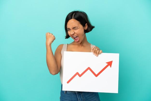 成長する統計矢印記号と強いジェスチャーをしている看板を保持している青い背景で隔離の若い混血の女性