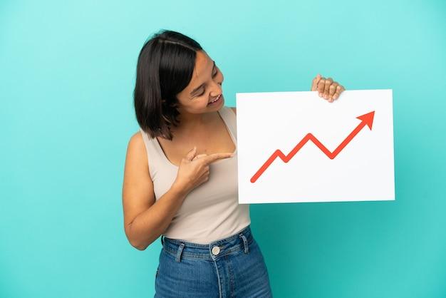 青い背景に分離された若い混血の女性が、成長している統計矢印記号の付いた看板を持ち、それを指している