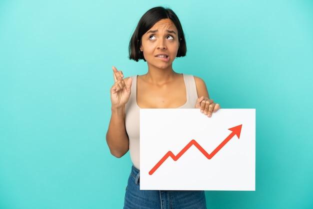 指が交差する統計矢印記号が成長している看板を保持している青い背景で隔離の若い混血の女性