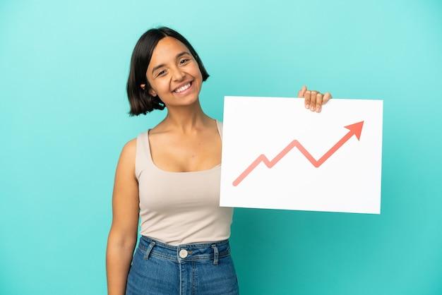 幸せな表現と成長統計矢印記号のサインを保持している青い背景で隔離の若い混血の女性