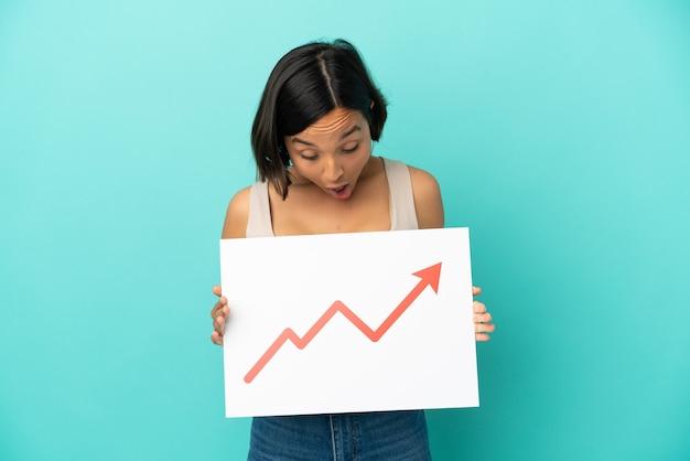 驚いた表情で成長統計矢印記号の看板を保持している青い背景で隔離の若い混血の女性