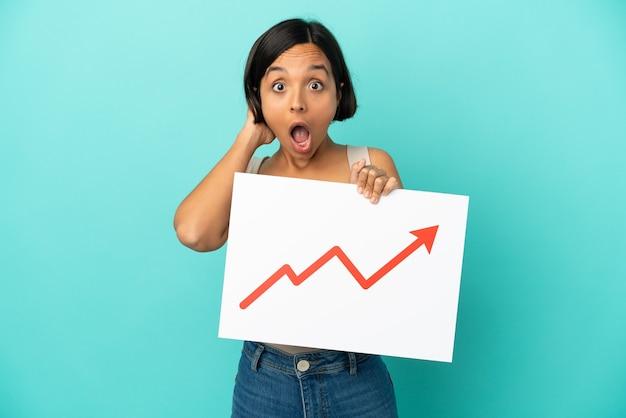 驚いた表情で成長する統計矢印記号のサインを保持している青い背景で隔離の若い混血の女性