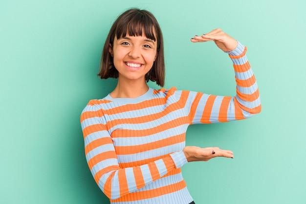 젊은 혼합 된 경주 여자 웃 고 자신감, 집게 손가락으로 뭔가 조금 들고 파란색 배경에 고립.