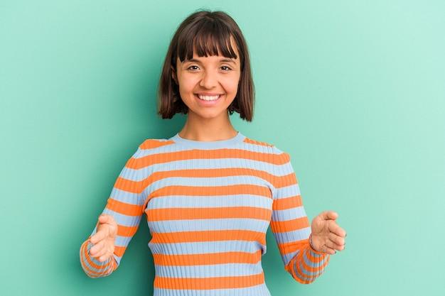 제품 프레 젠 테이 션 양손으로 뭔가 들고 파란색 배경에 고립 된 젊은 혼합 된 경주 여자.