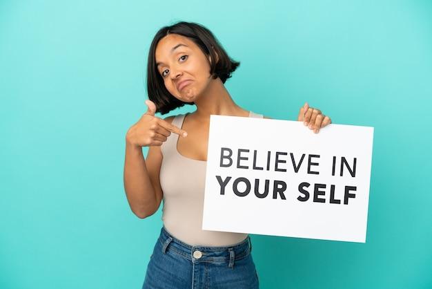 Молодая женщина смешанной расы изолирована на синем фоне, держа доску we want you и указывая на нее