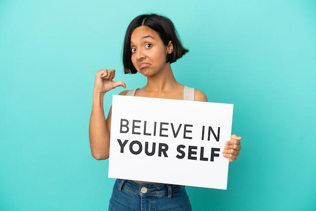 Молодая женщина смешанной расы, изолированная на синем фоне, держит доску we want you с гордым жестом