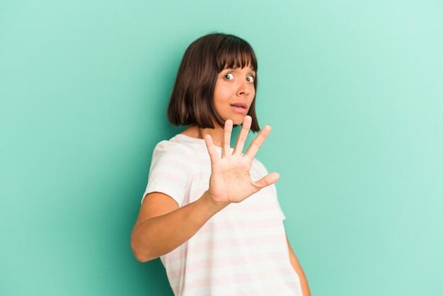 파란색 배경에 고립 된 젊은 혼혈 여자는 빈 공간을 보여주는 두 앞 손가락으로 나타냅니다.