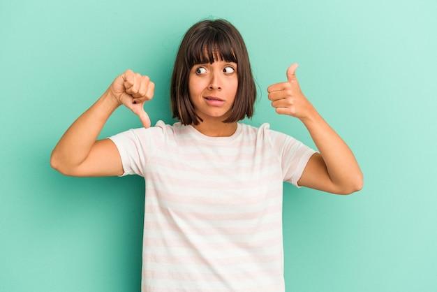 Молодая женщина смешанной расы, изолированные на синем фоне, держит руки под подбородком, счастливо смотрит в сторону.
