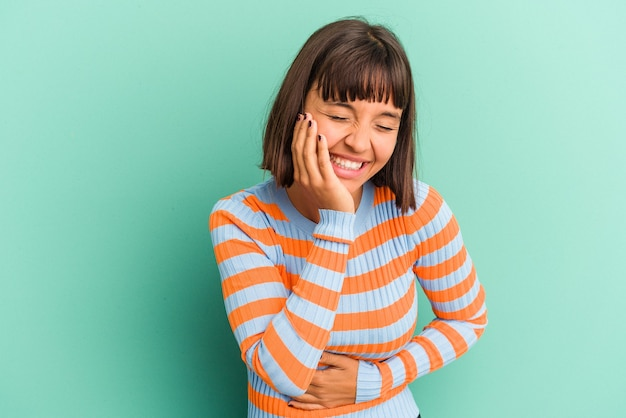 웃으면 서 재미 파란색 배경에 고립 된 젊은 혼합 된 경주 여자.