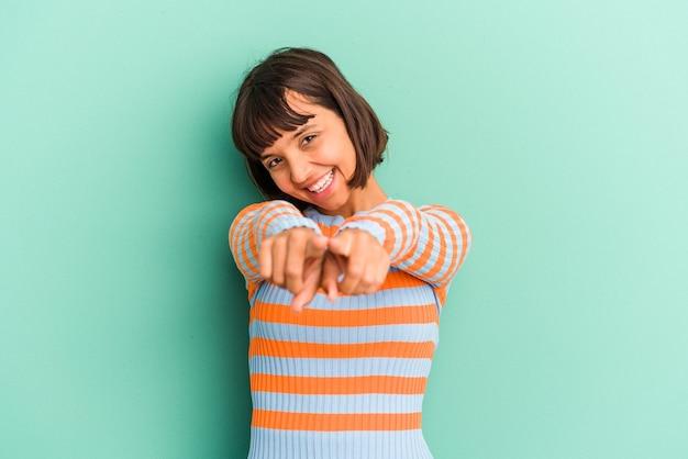 青の背景に分離された若い混血の女性が指で正面を指しています。