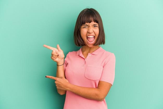 흥분과 욕망을 표현하는 집게 손가락으로 복사 공간을 가리키는 파란색 배경에 고립 된 젊은 혼합 된 인종 여자.