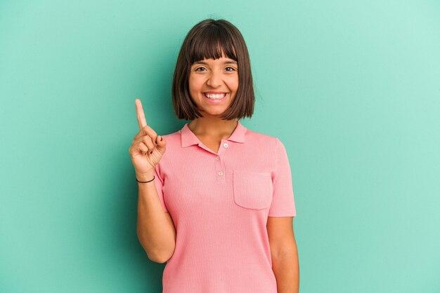 손가락으로 번호 하나를 보여주는 파란색 배경에 고립 된 젊은 혼합 된 인종 여자.