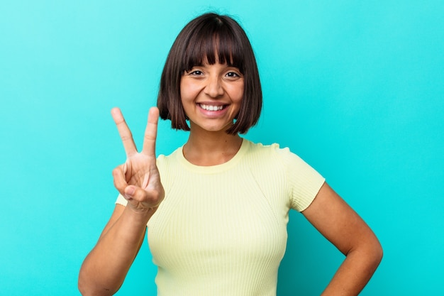 青い背景に分離された若い混血の女性は、勝利のサインを示し、広く笑っています。