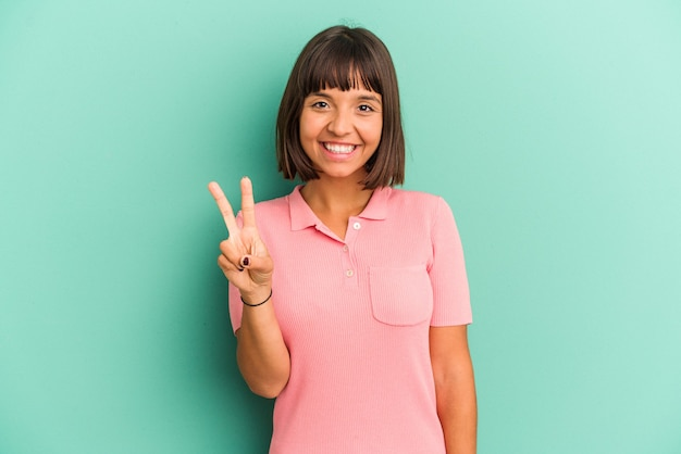 승리 기호를 표시 하 고 광범위 하 게 웃 고 파란색 배경에 고립 된 젊은 혼합 된 인종 여자.