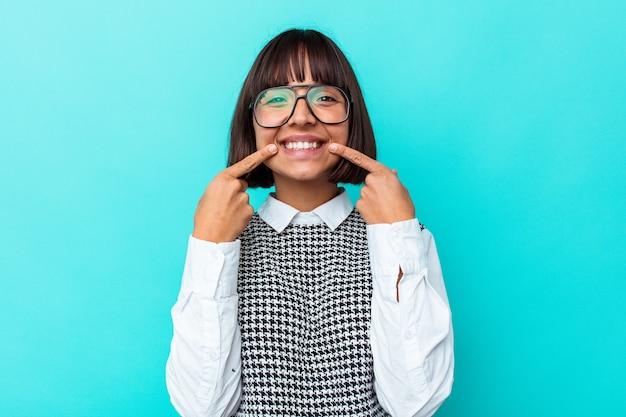 입에서 손가락을 가리키는 파란색 배경 미소에 고립 된 젊은 혼합 된 인종 여자.