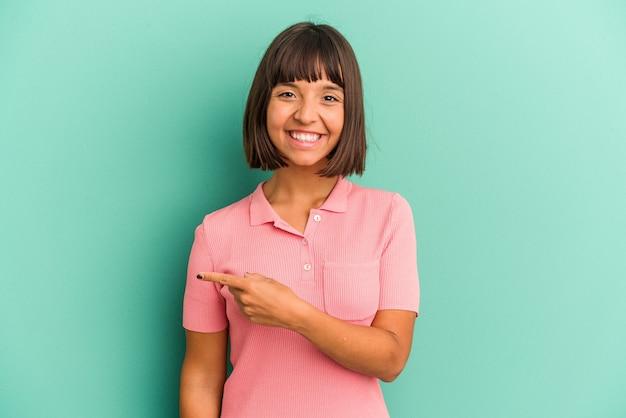 웃 고 옆으로 가리키는 파란색 배경에 고립 된 젊은 혼합 된 인종 여자 빈 공간에서 뭔가 보여주는.