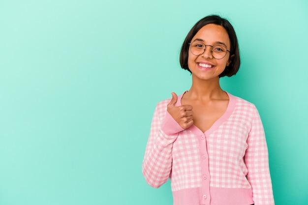 Молодая женщина смешанной расы изолирована на синем фоне, улыбаясь и поднимая палец вверх