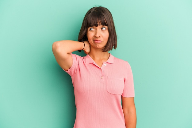 젊은 혼혈 여자 머리를 다시 만지고, 생각 하 고 선택을 파란색 배경에 고립.