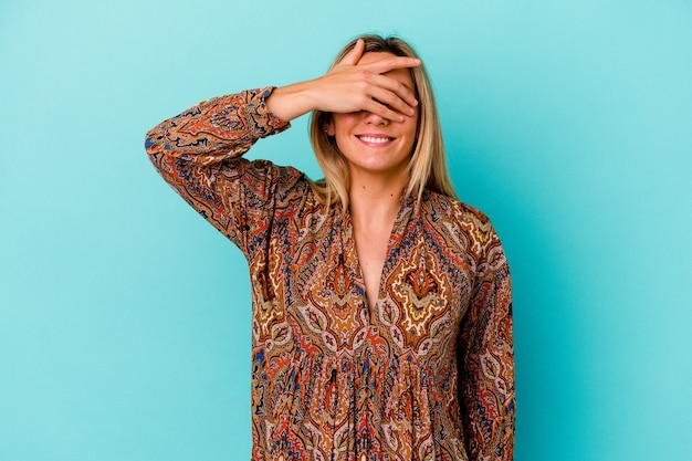Молодая женщина смешанной расы изолирована на голубых прикрывает глаза руками, широко улыбается, ожидая сюрприза.