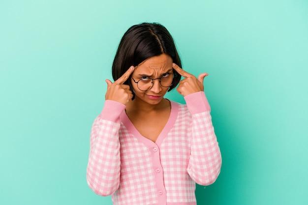 파란색에 고립 된 젊은 혼합 된 인종 여자는 작업에 초점을 맞춘 집게 손가락이 머리를 가리키는 유지.