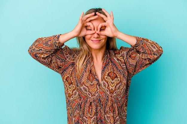 Молодая женщина смешанной расы изолирована на синем, держа глаза открытыми, чтобы найти возможность успеха.