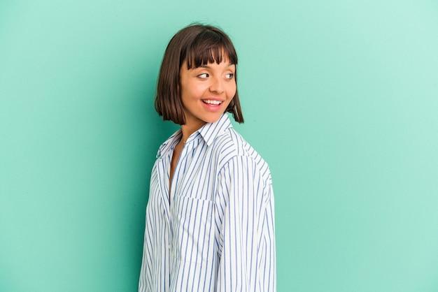 青で隔離された若い混血の女性は、笑顔、陽気で楽しい脇に見えます。 Premium写真
