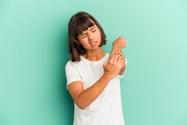 青いマッサージ肘で孤立した若い混血の女性は、悪い動きの後に苦しんでいます。