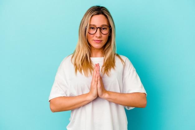 Молодая женщина смешанной расы изолирована на синем, молясь, показывая преданность, религиозный человек ищет божественное вдохновение.