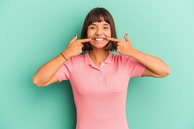 푸른 미소에 고립 된 젊은 혼합 된 인종 여자 입에서 손가락을 가리키는.