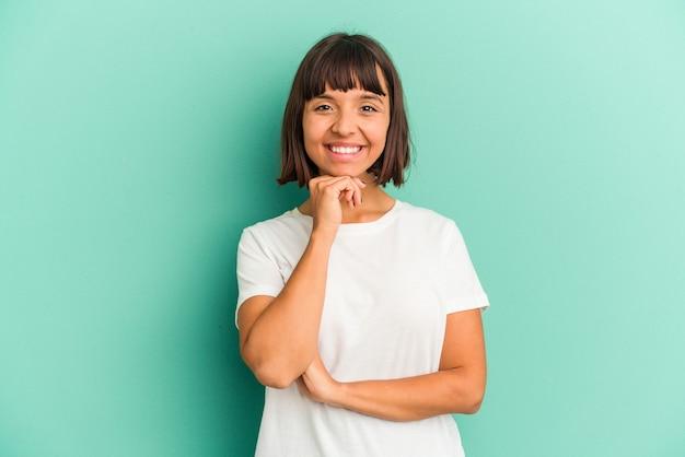 青で孤立した若い混血の女性は、手で顎に触れて、幸せで自信を持って笑っています。