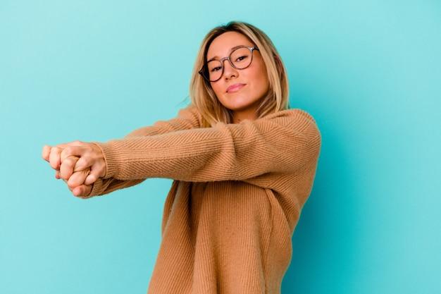 Молодая женщина смешанной расы изолирована на синем растяжении рук, расслабленном положении.