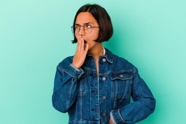 Молодая женщина смешанной расы изолирована на синей стене, зевая, показывая усталый жест, закрывающий рот рукой.
