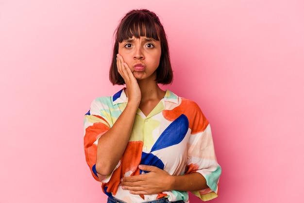 ピンクの背景に分離された若い混血の女性は頬を吹く、疲れた表情をしています。表情のコンセプト。