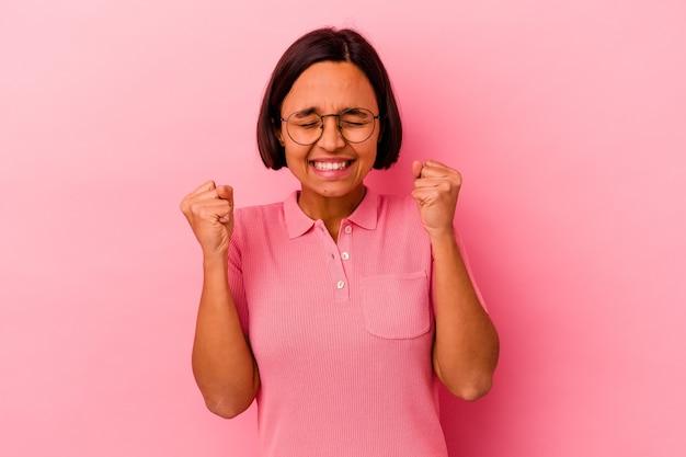 勝利、情熱と熱意、幸せな表現を祝うピンクの背景に分離された若い混血の女性。